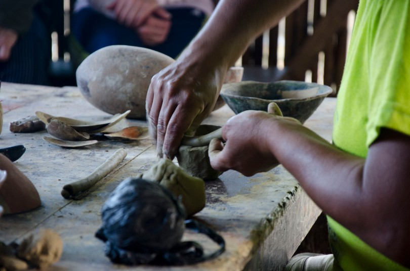 A coil of clay is quickly transformed into the base of a bowl.