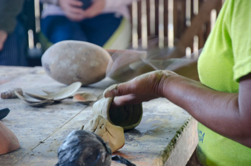 The camera captures the swift hand movements needed to smooth the outside of the clay bowl.