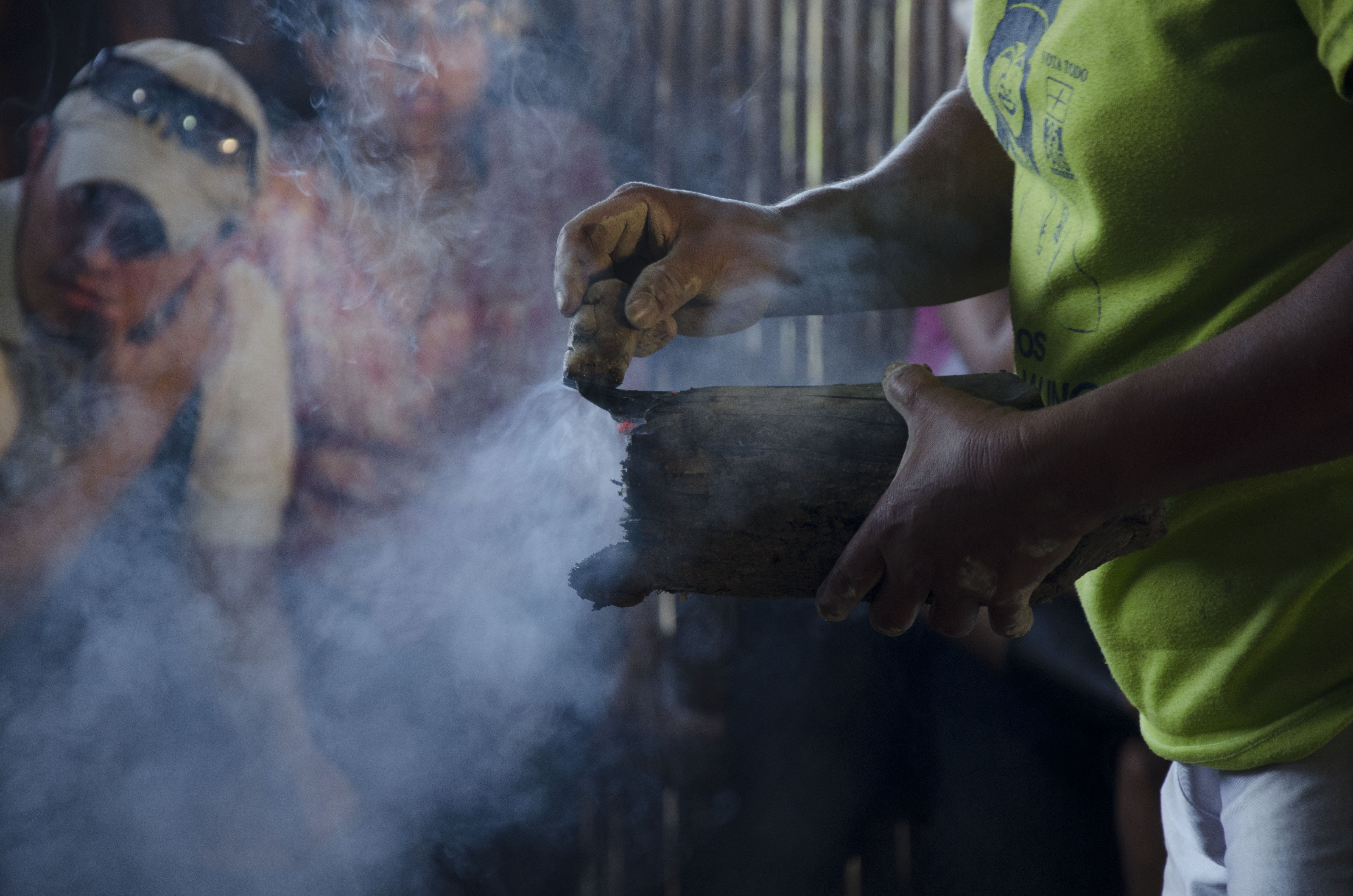 A small piece of wood is heated to release the natural resin which is then applied to the burnished pot.