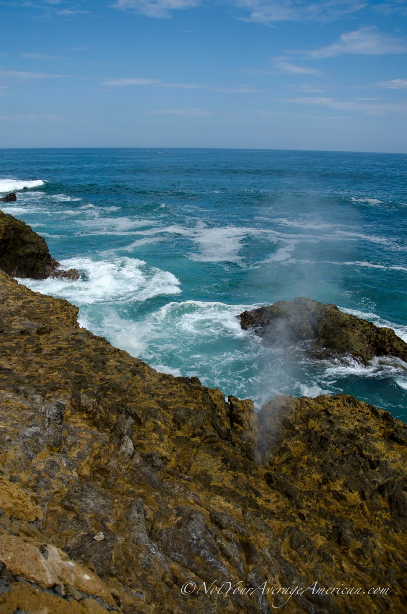 Water vapor forced through a small whole as the waves crash against the rocks at La Chocolatera, Salinas