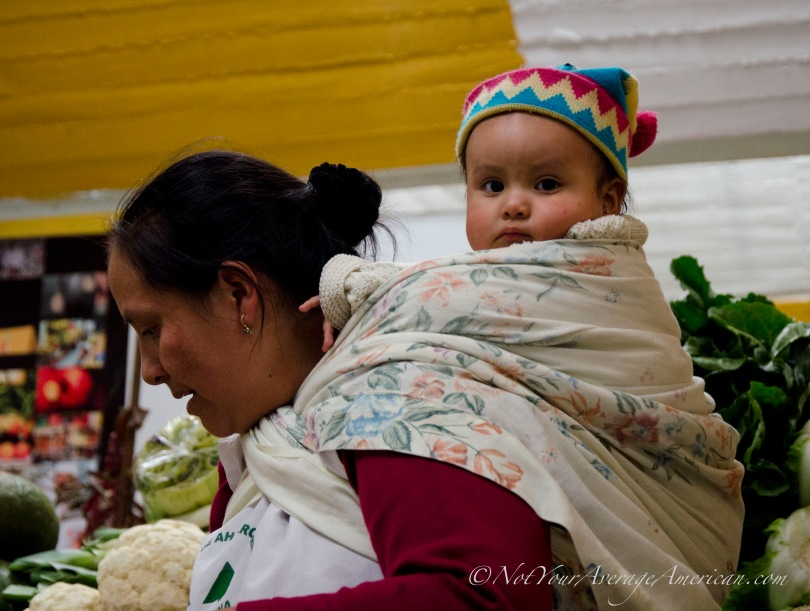 Young Madeline stays out of trouble while her mom, Lourdes, fills a bag of tomatoes. Babies and toddlers are a common sight in all of Ecuador, but especially in places where mothers work.