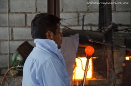Jhonaton blowing on hot glass.