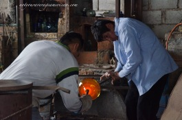 Johan and Jhonathan work together on shaping a piece of hot glass.